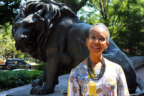 2019 Julie Klauber Award Winner - Brenda Boyd (standing in front of a lion statue)